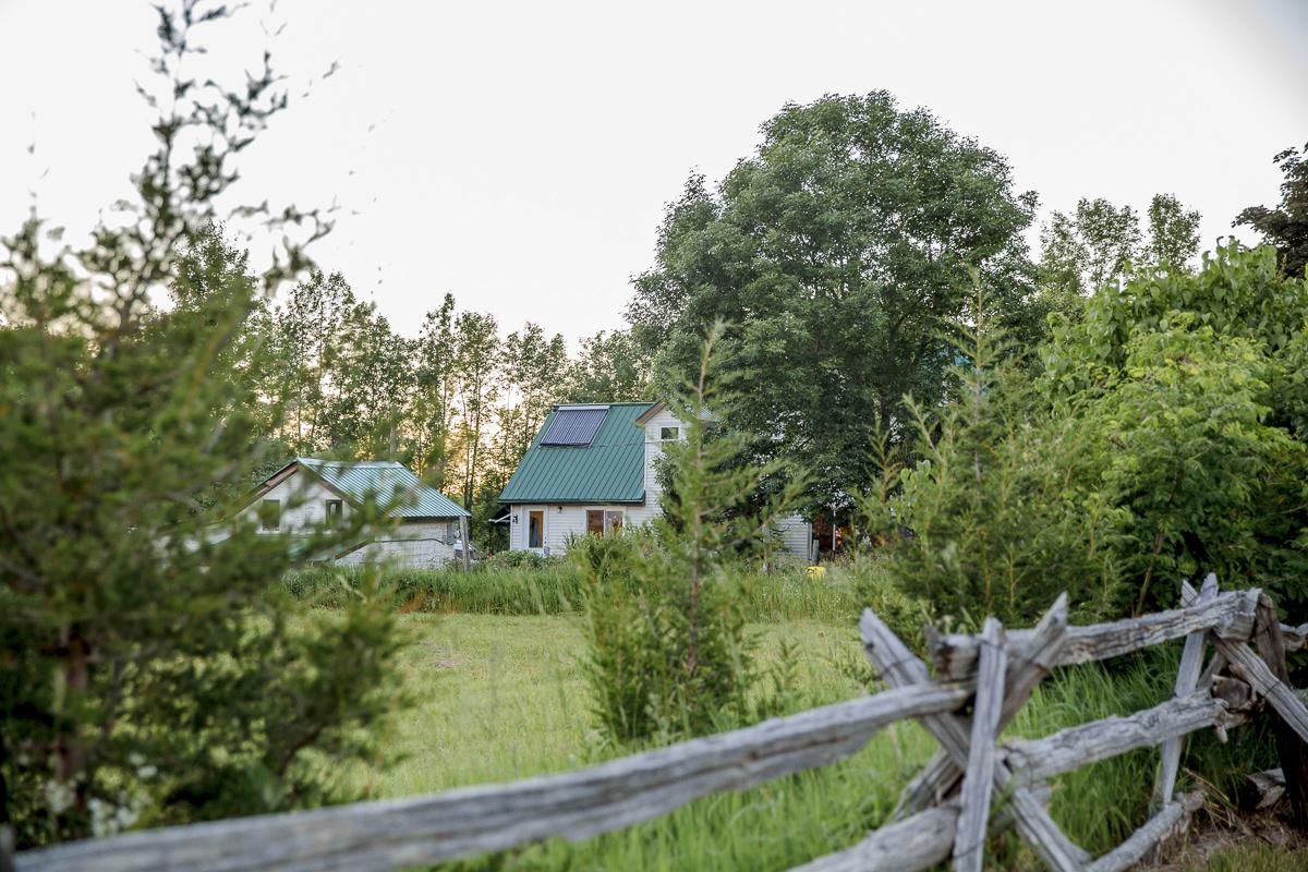 Farmhaus in Kanada umgeben von grünen Bäumen und Sträuchern