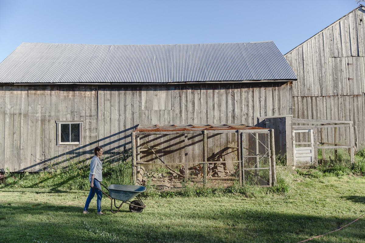Liz Huntly mit Schubkarre bei der Gartenarbeit auf ihrer Farm in Kanada