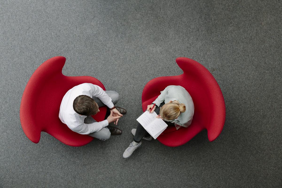 von oben fotografiert: 2 Kollegen sitzen auf roten Sesseln und besprechen sich