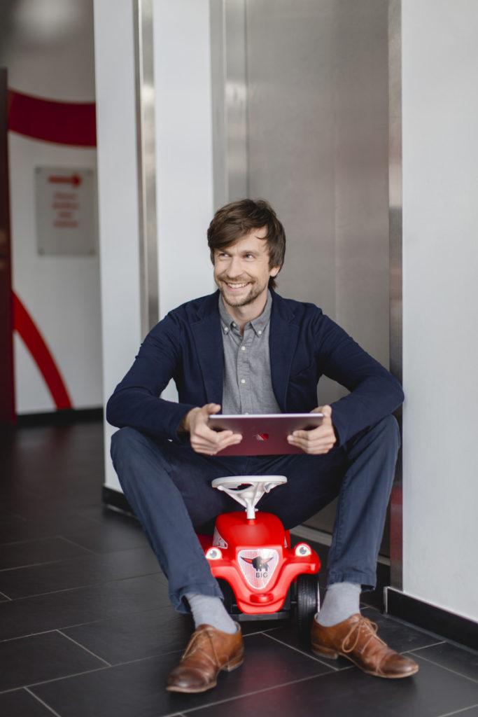 Mitarbeiterportrait eines Mannes, der mit einem Tablet auf einem Bobby Car sitzt