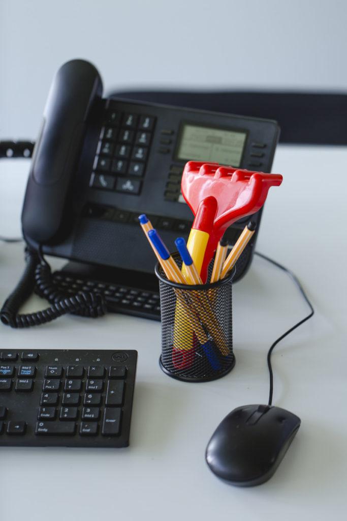Nahaufnahme Schreibtisch mit Stiften, Telefon, Tastatur und Computer-Maus