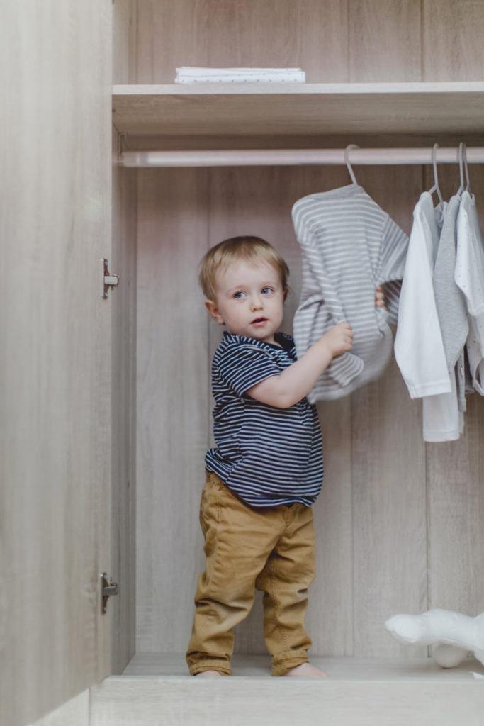 kleines Kind im Kleiderschrank