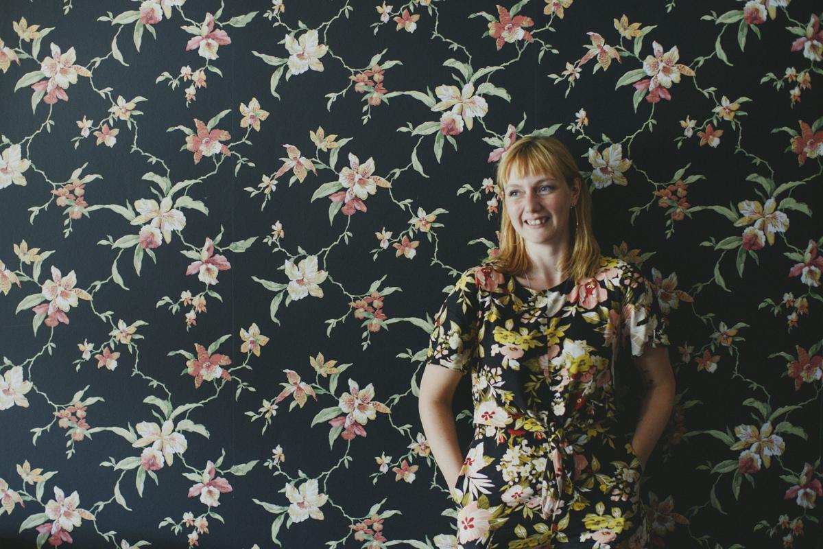 Portraitfoto einer jungen Frau vor einer Blumentapete