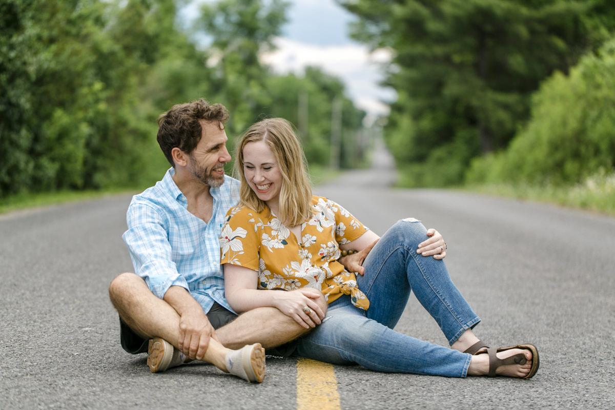 Portraitfoto eines glücklichen Paares, das aneinander gekuschelt auf der Straße sitzt