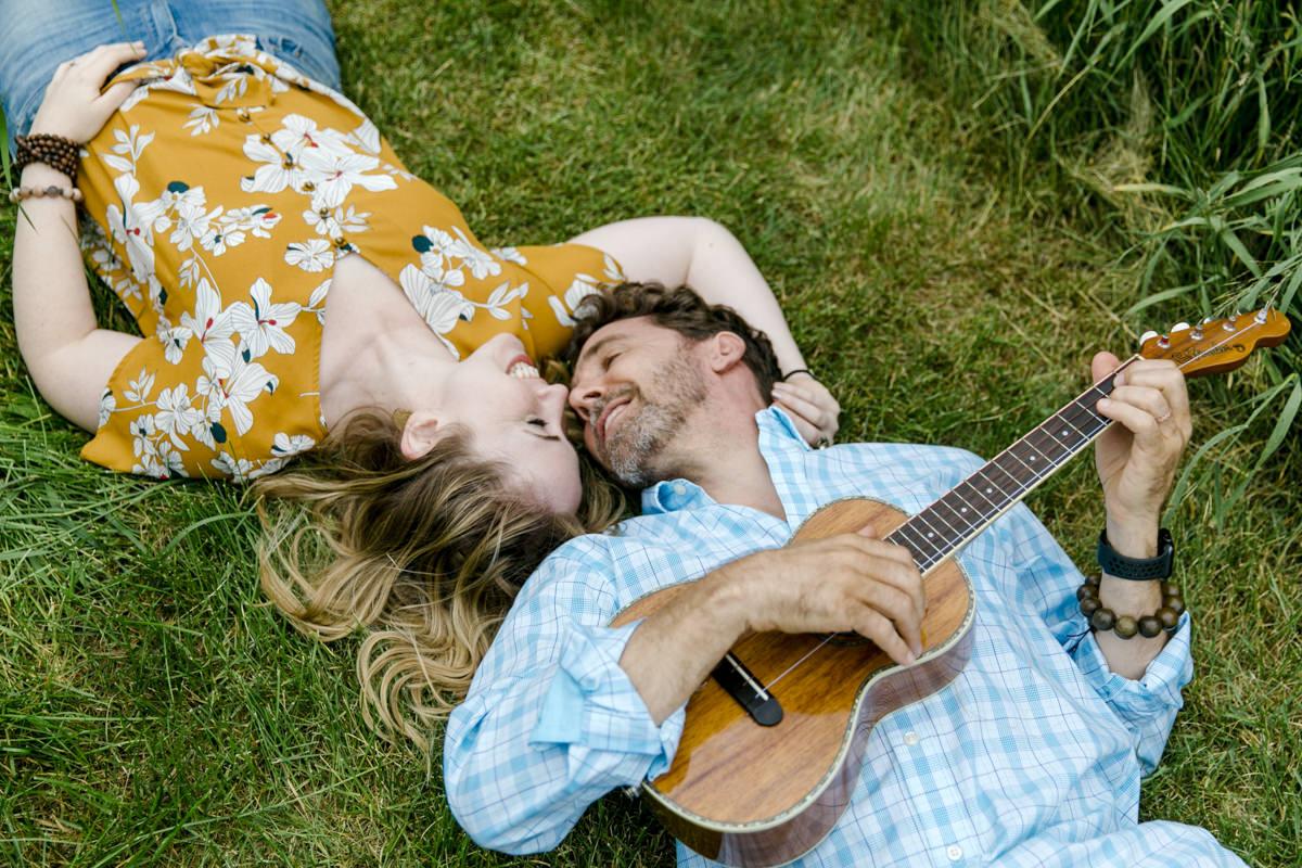 Portraitfoto eines verliebten Paares, das mit Gitarre auf einer Wiese liegt