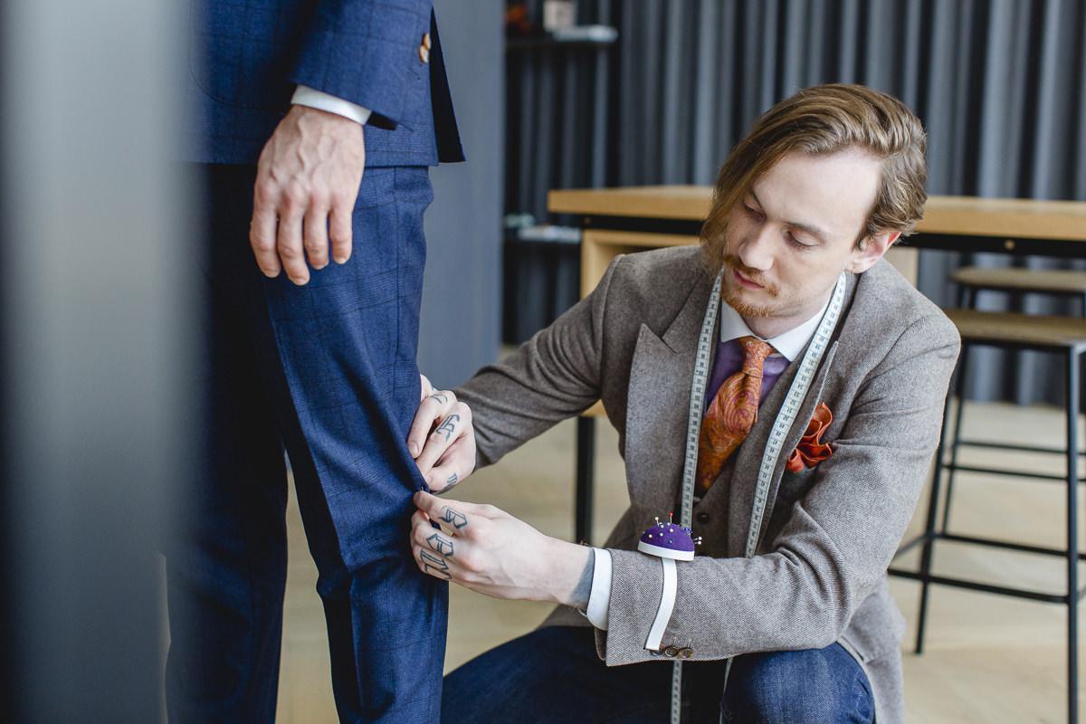 ein Herrenmaßschneider von The Bloke steckt die Hose eines Kunden ab | fotografiert von Hanna Witte