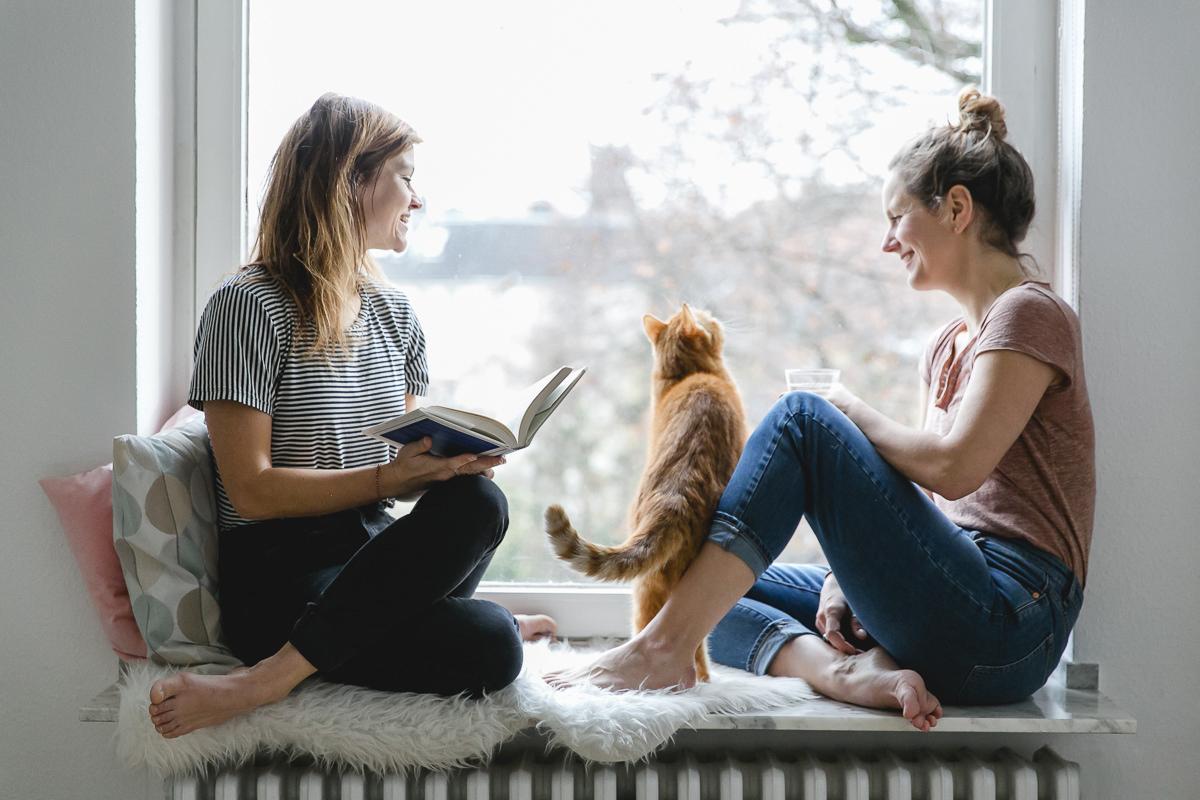 Portraitfoto von 2 Frauen, die mit einer Katze am Fenster sitzen und ein Buch lesen