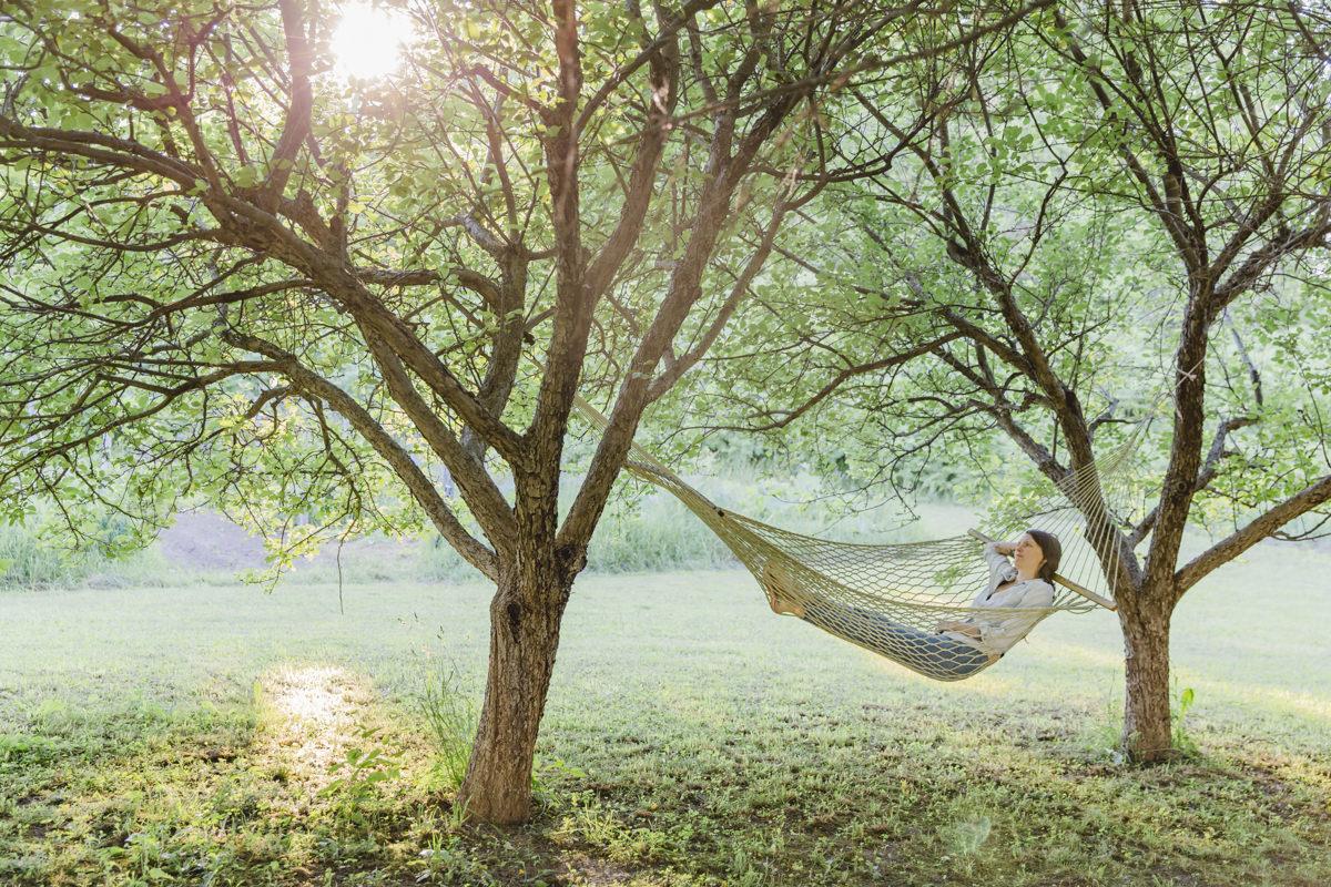 Liz Huntly liegt in einer Hängematte zwischen zwei Bäumen in der Sonne Kanadas