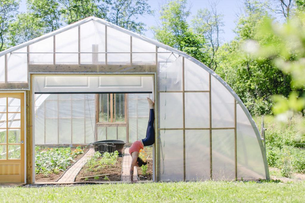 Liz Huntly macht einen Handstand am Gewächshaus ihrer Farm in Kanada