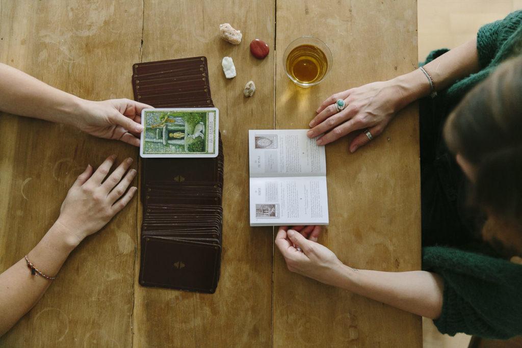 2 Frauen legen sich die Karten und deuten sie mit einem Buch