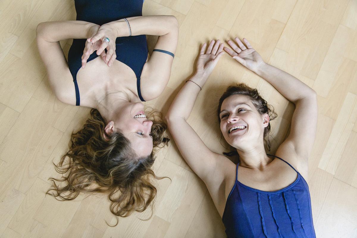 sympathisches Portrait von den Yoga Lehrerinnen Steffi Grube und Daniela Kourtidis, die entspannt auf dem Boden liegen