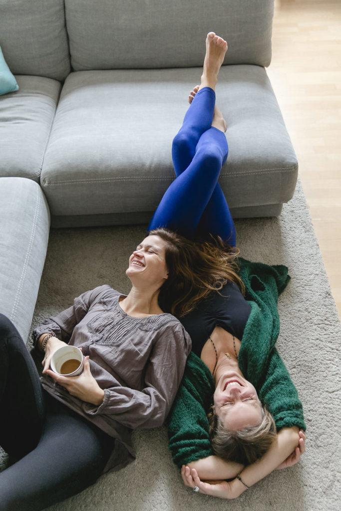 entspanntes Portraitbild der Yoga Lehrerinnen Steffi Grube und Daniela Kourtidis, die auf dem Boden liegen