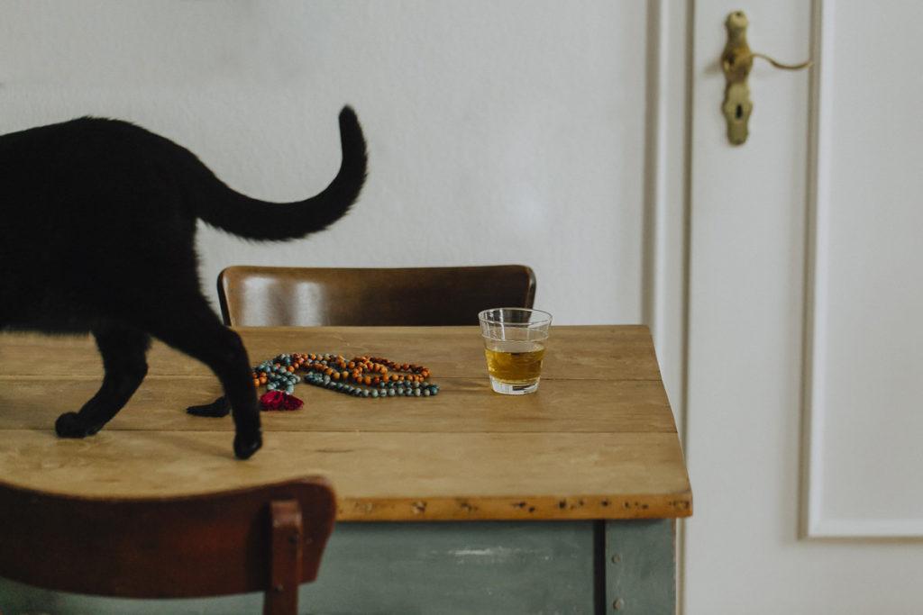 eine schwarze Katze läuft über einen Holztisch