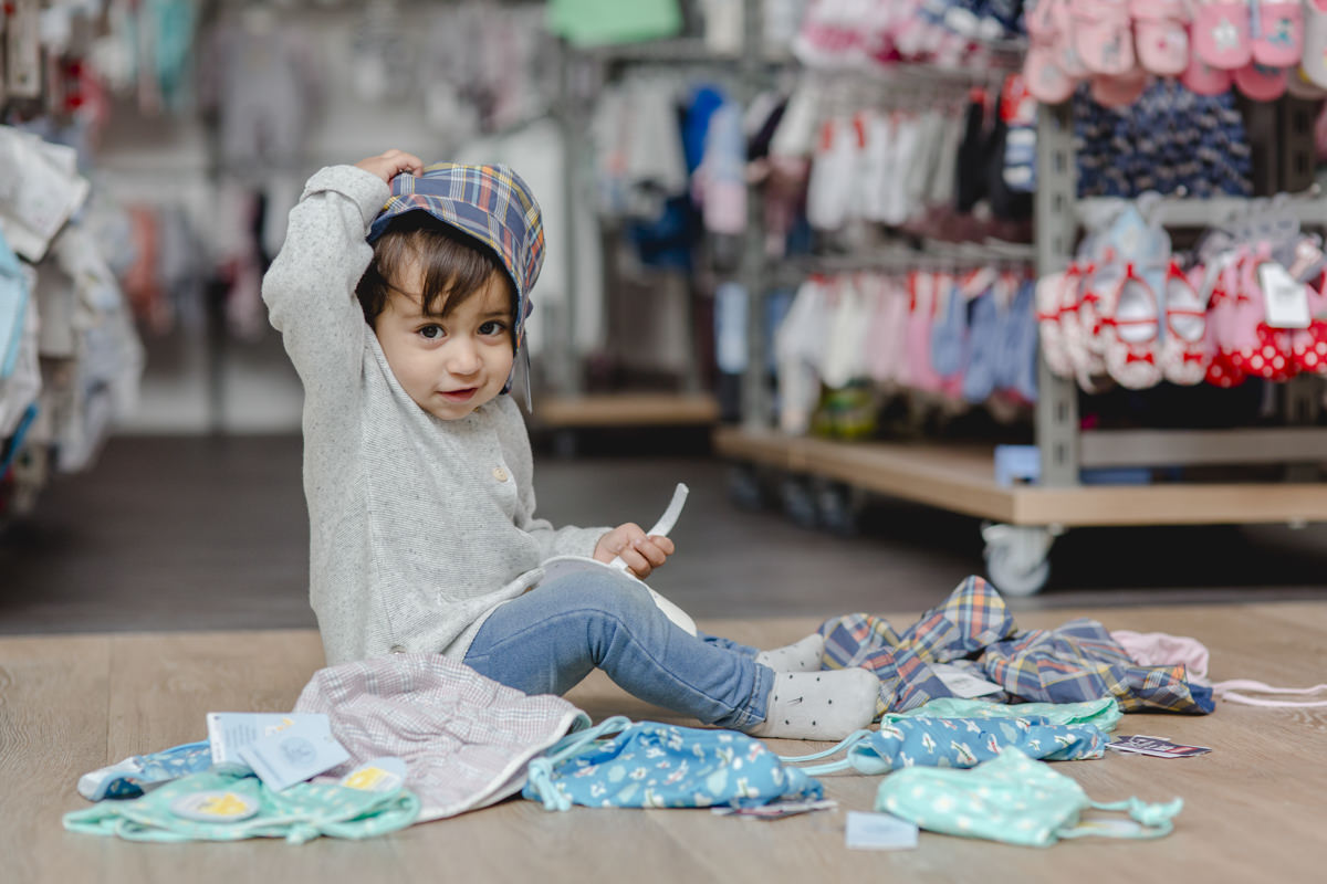 niedliches Kleinkind spielt mit Kinderbekleidung von Babyone
