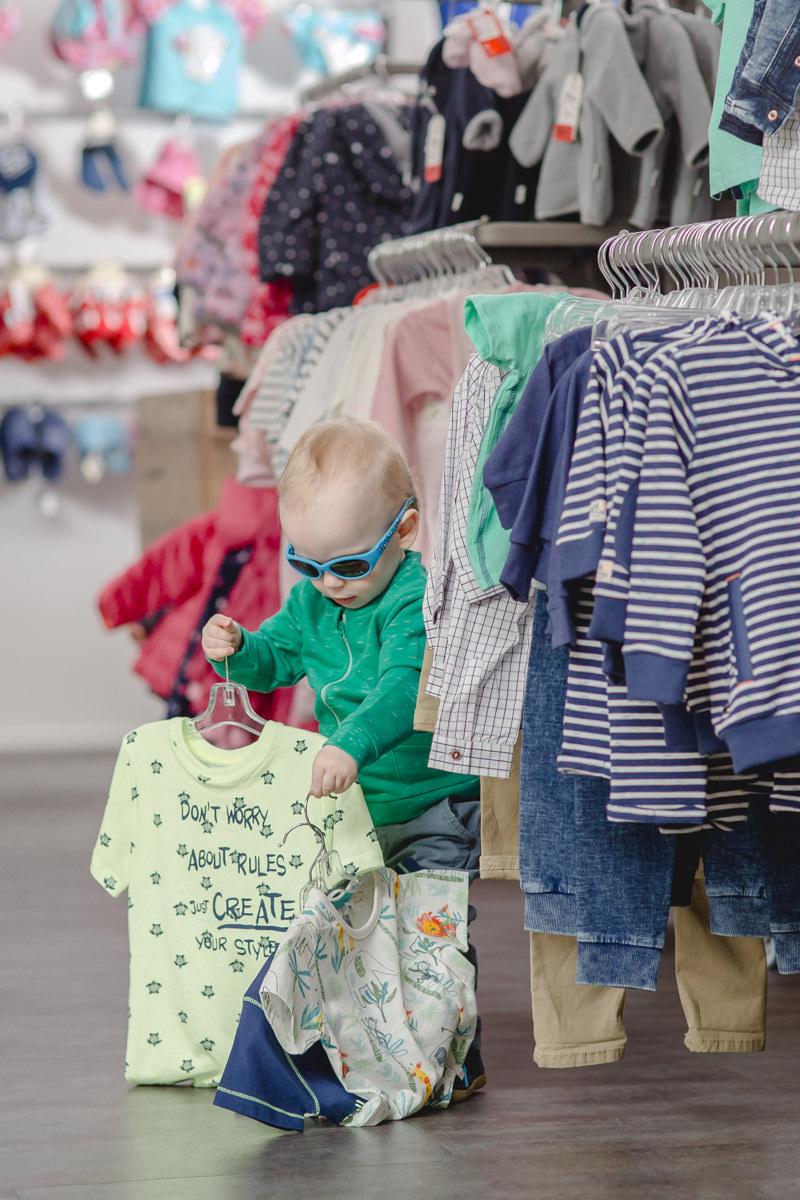 süßes Kleinkind mit Sonnenbrille spielt mit Kinderbekleidung von Babyone