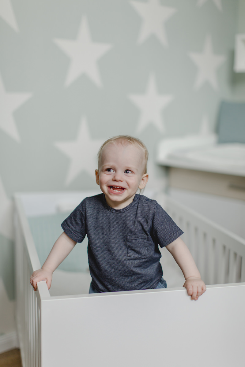 süßes Kleinkind steht in einem Kinderbett von Babyone