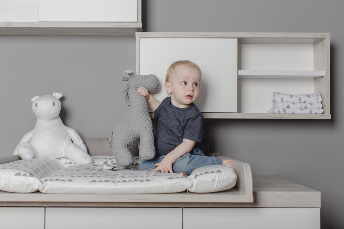 niedliches Kleinkind mit Kuscheltier auf einem Wickeltisch von Babyone