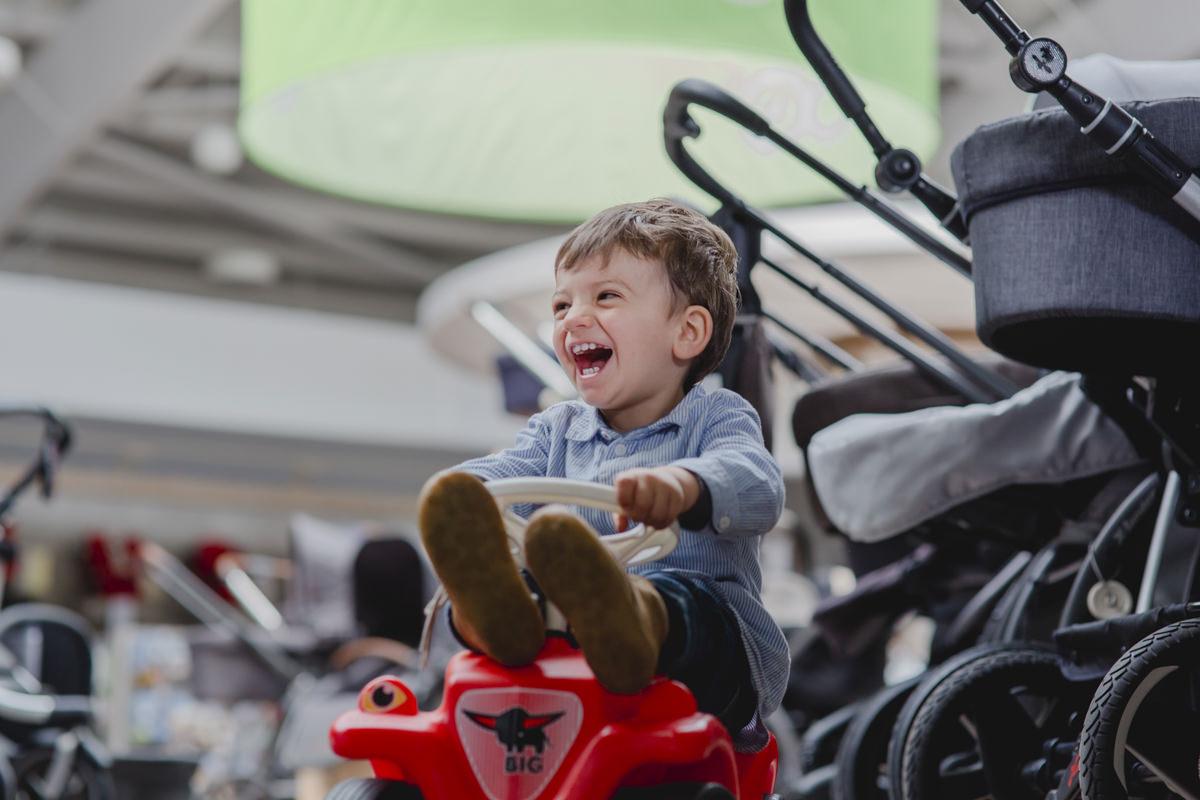 lachendes Kind auf einem Bobby Car