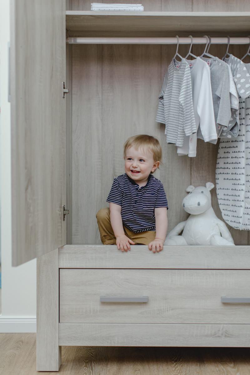 süßes Kleinkind sitzt in einem Kleiderschrank von Babyone