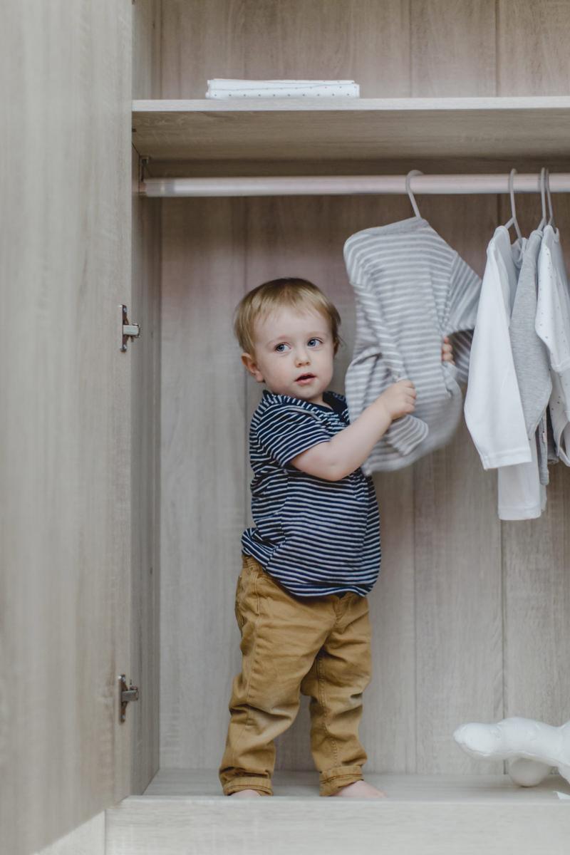 niedliches Kleinkind spielt in einem Schrank mit Kinderbekleidung von Babyone