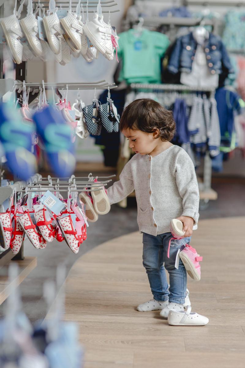 Kleinkind sieht sich die Schuhe im Babyone Geschäft an