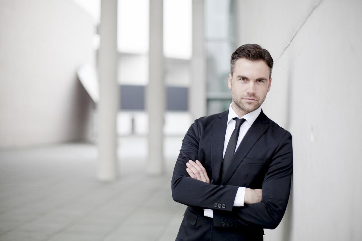authentisches Business Portrait eines jungen Mannes im Anzug, der locker gegen eine Wand lehnt