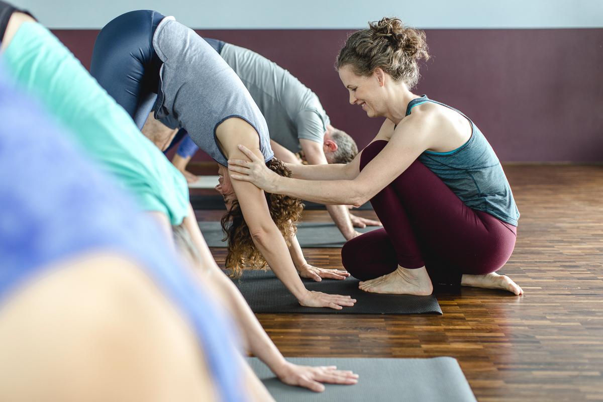 Yogalehrerin hilft einer Schülerin bei einer Yoga Übung in der Yoga Schule Ginger Up in Köln