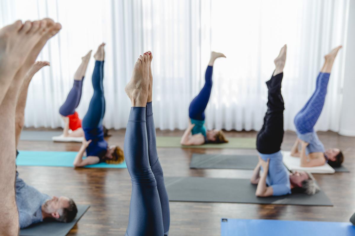 Teilnehmer machen eine Übung in einem Yoga Kurs im Yoga Studio Ginger Up in Köln