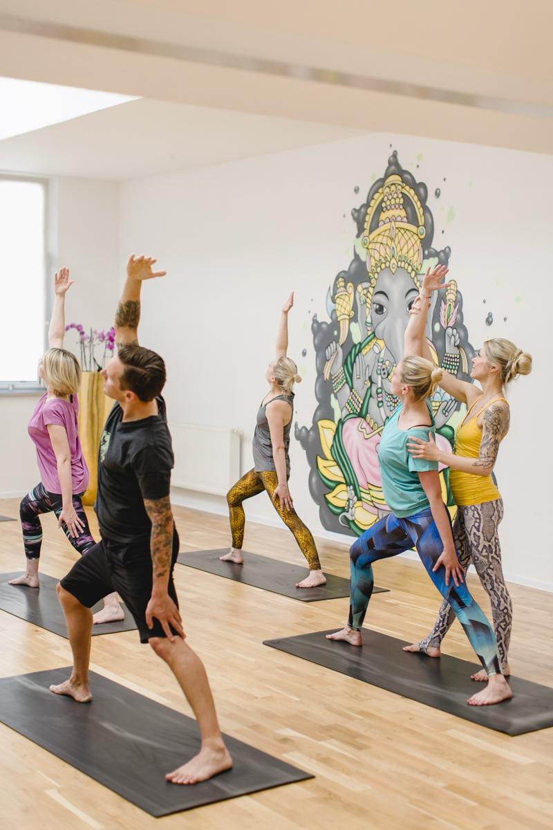 Kursteilnehmer machen eine Yoga Übung unter Anleitung in einem Yoga Studio in Neuss