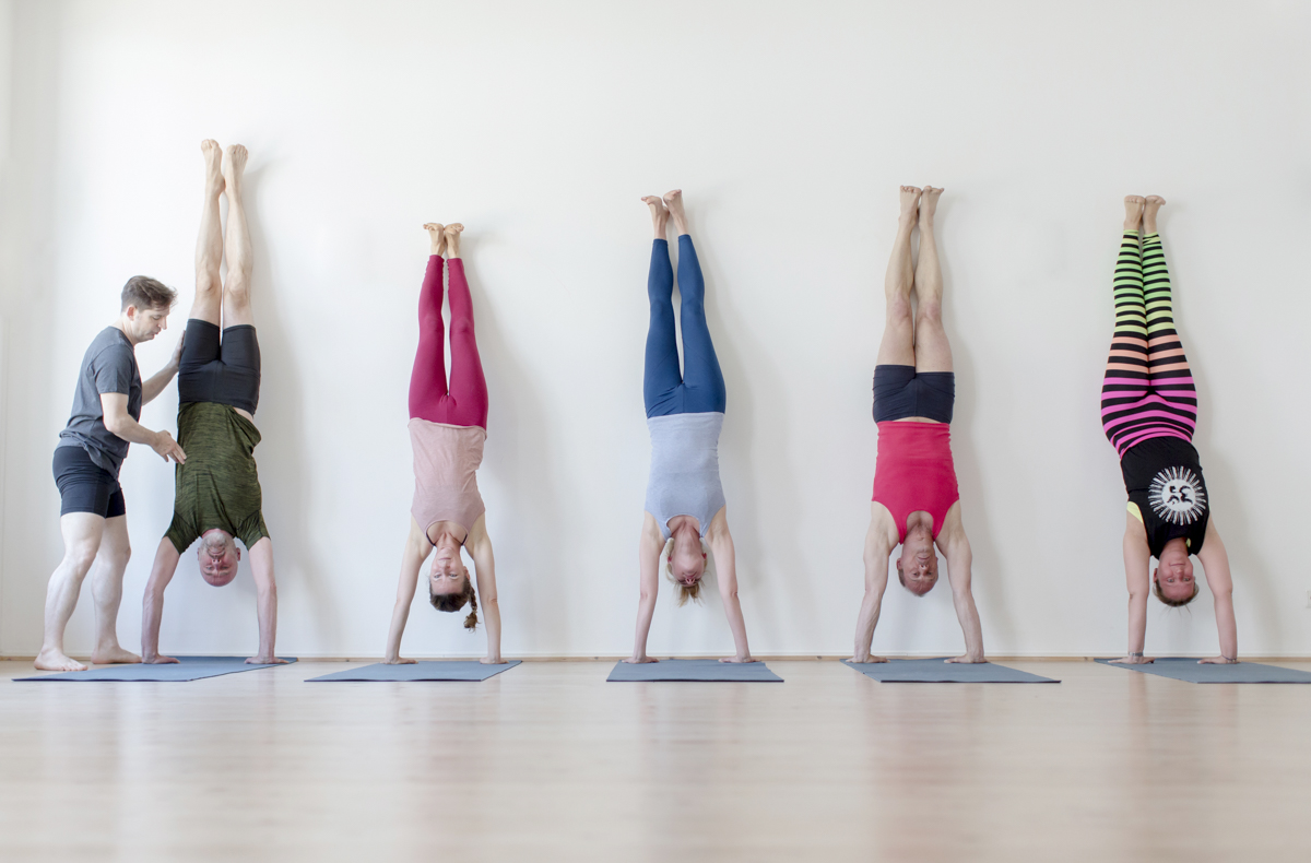 Teilnehmer machen einen Handstand in einem Yoga Kurs im Yoga Studio Shivas Loft in Düsseldorf