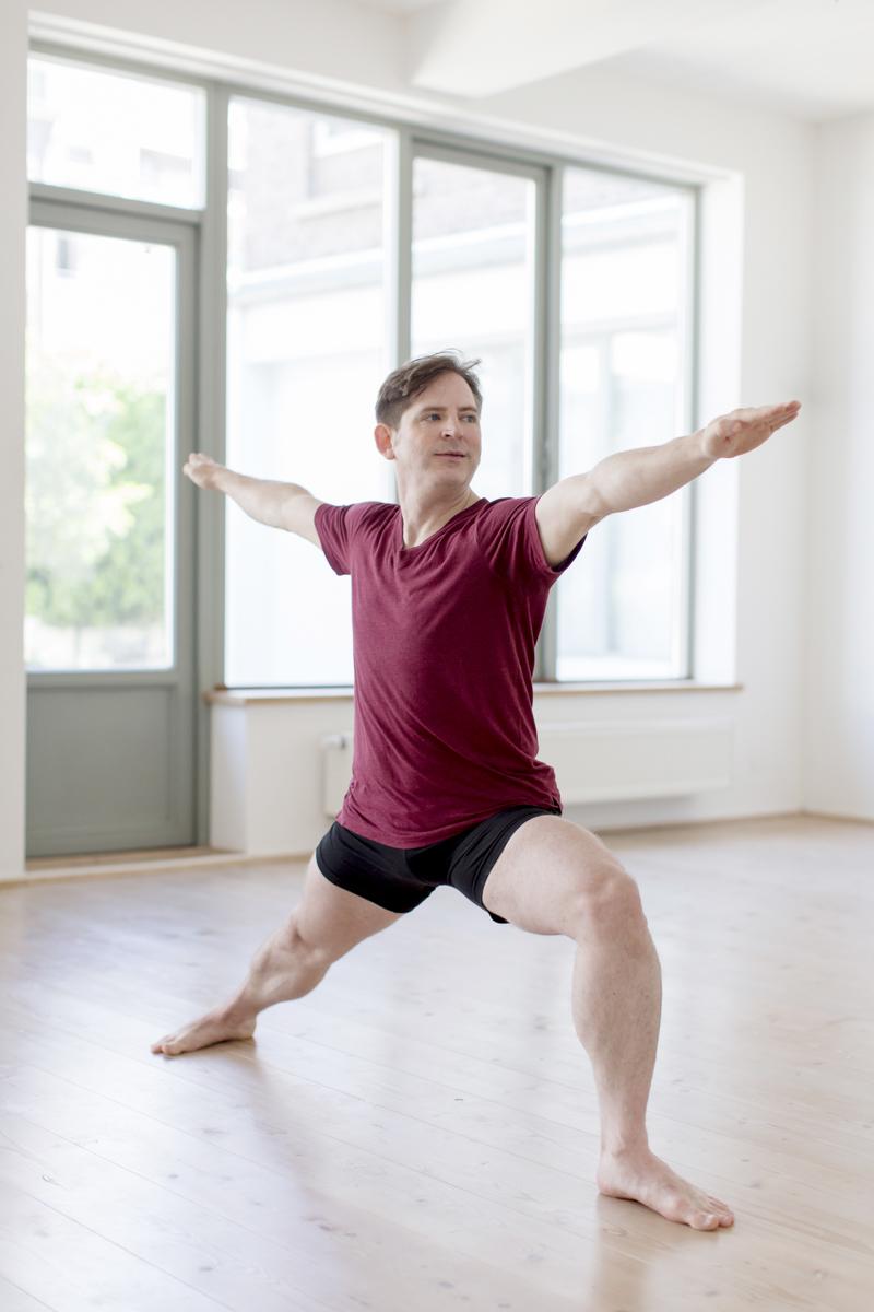 authentisches Portrait eines Yoga Lehrers bei einer Übung