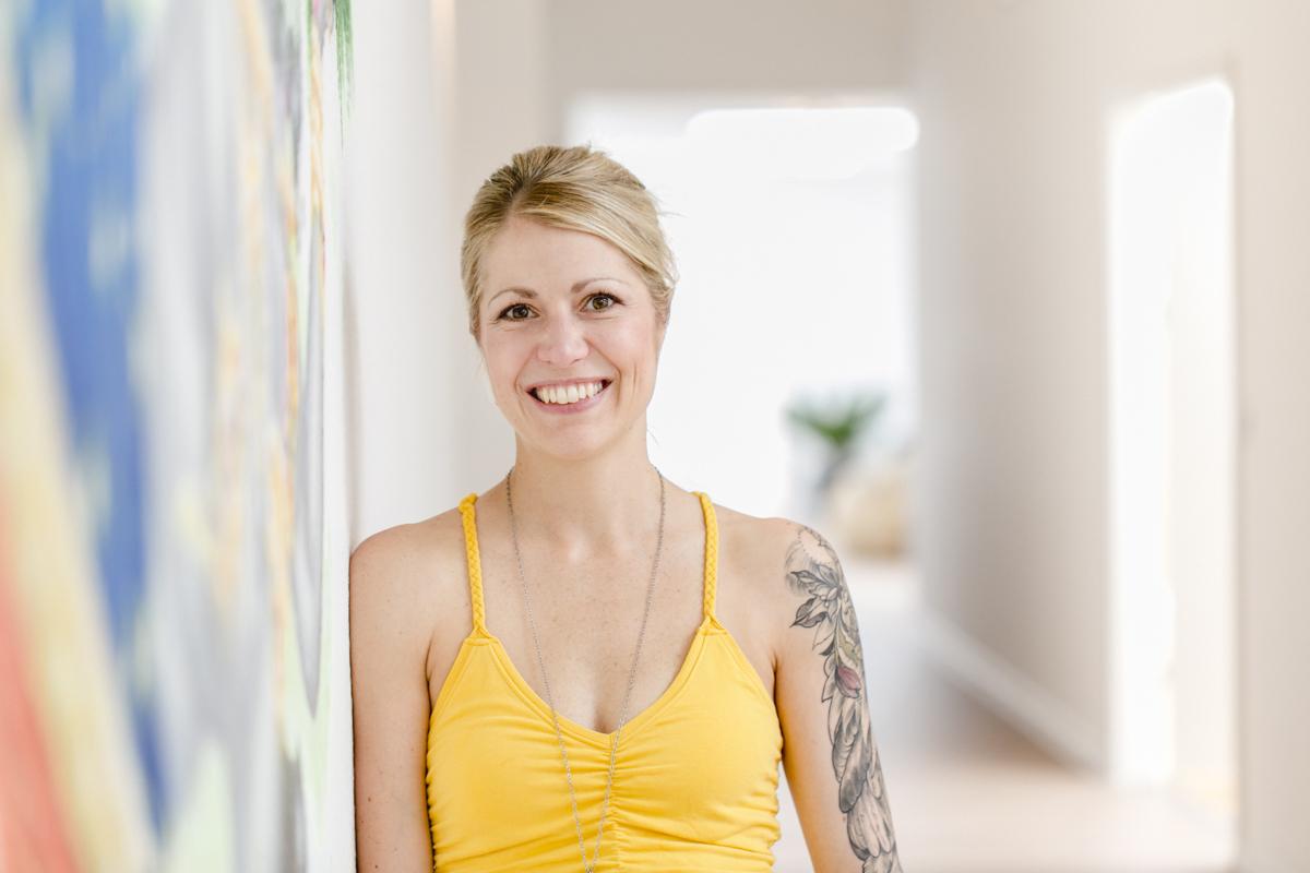 freundliches Portrait Bild einer Yoga Lehrerin in ihrem Yoga Studio