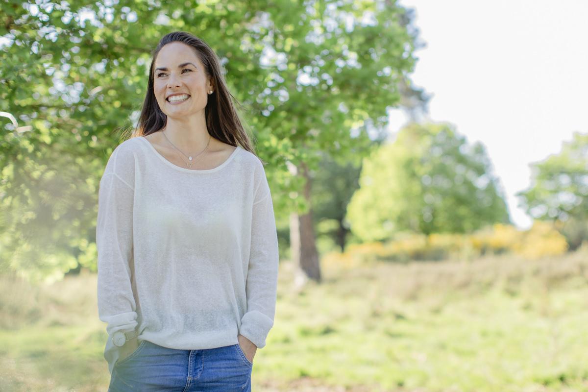 freundliches Portraitfoto eines weiblichen Meditations Coach in der Natur