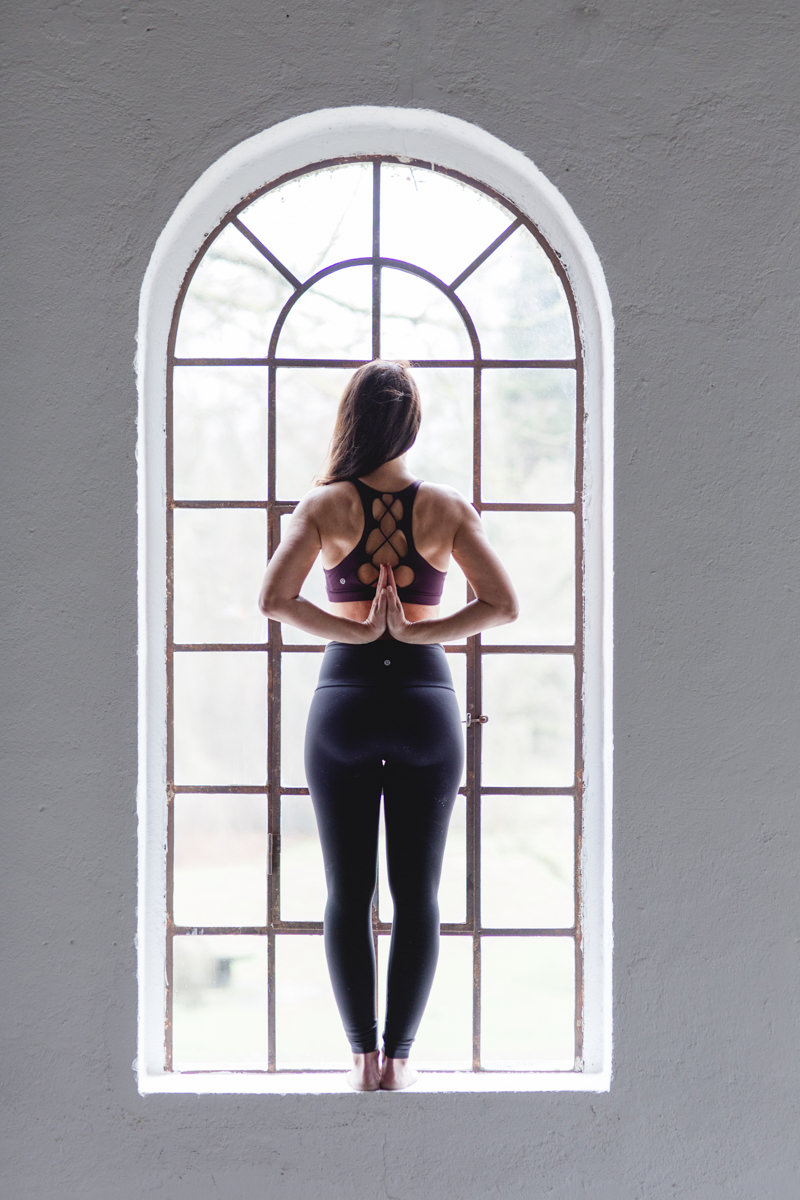 außergewöhnliches Yoga Portrait einer Yogalehrerin vor dem Fenster