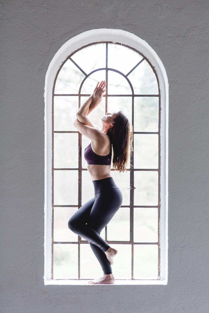 Beeindruckendes Portraitfoto einer Yoga Lehrerin bei einem Yoga Asana vor einem Fenster