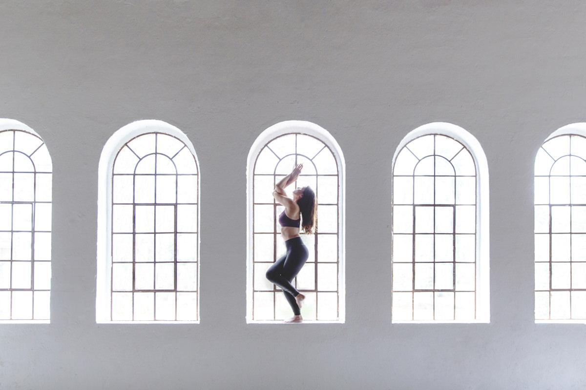 kreatives Portraitfoto einer Yoga Lehrerin vor einem Fenster