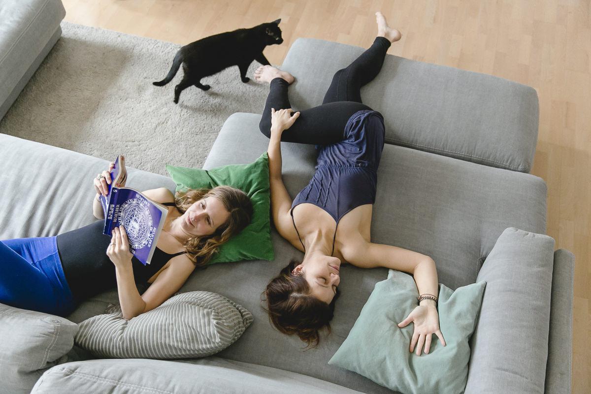 Portraitfoto von 2 Yogalehrerinnen, die auf einer Couch liegen