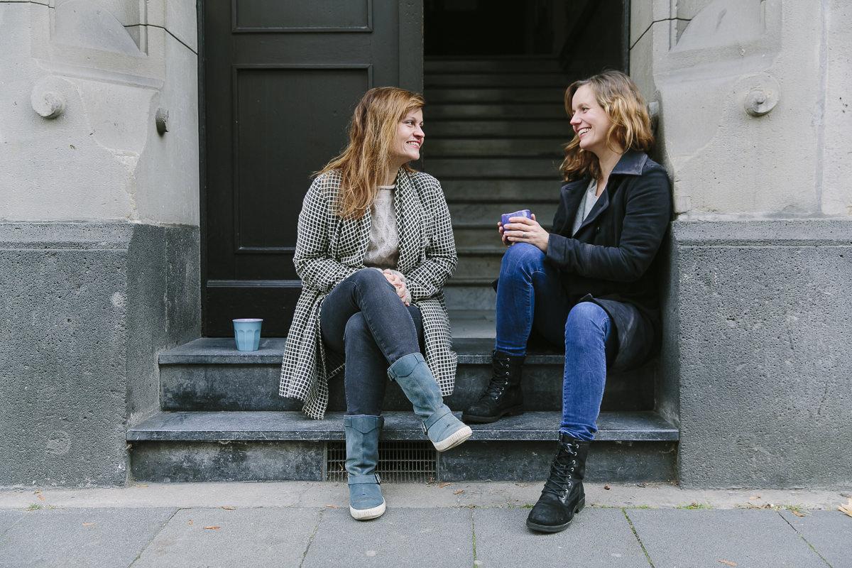 Portraitfoto der 2 Yogalehrerinnen von Holy, die auf einer Treppe sitzen