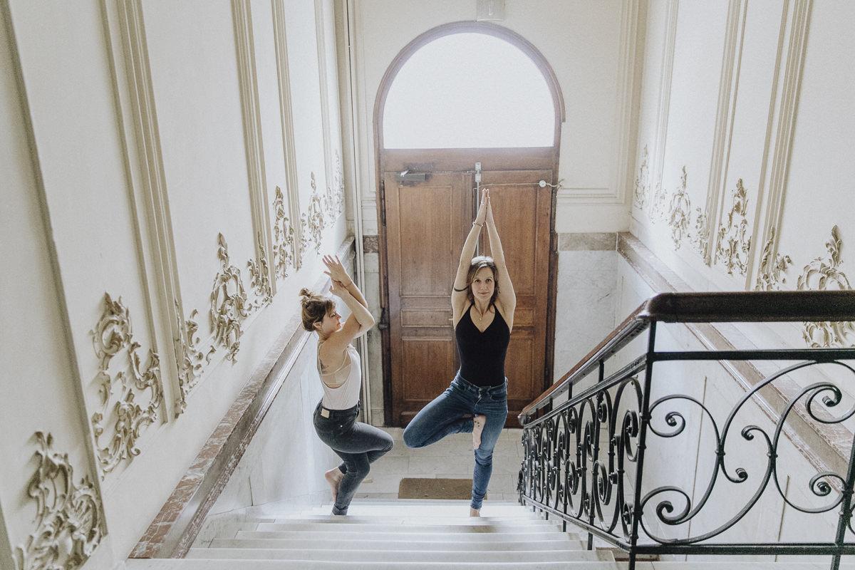 Yoga Foto der Gründerinnen von Holy Yoga während sie eine Yoga Übung in einem Treppenhaus zeigen