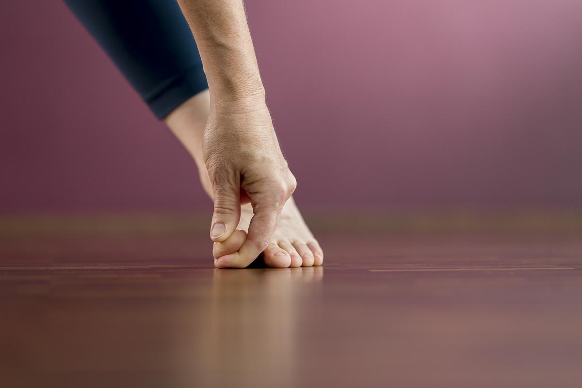 Hand berührt den Fuss bei einer Yoga Übung