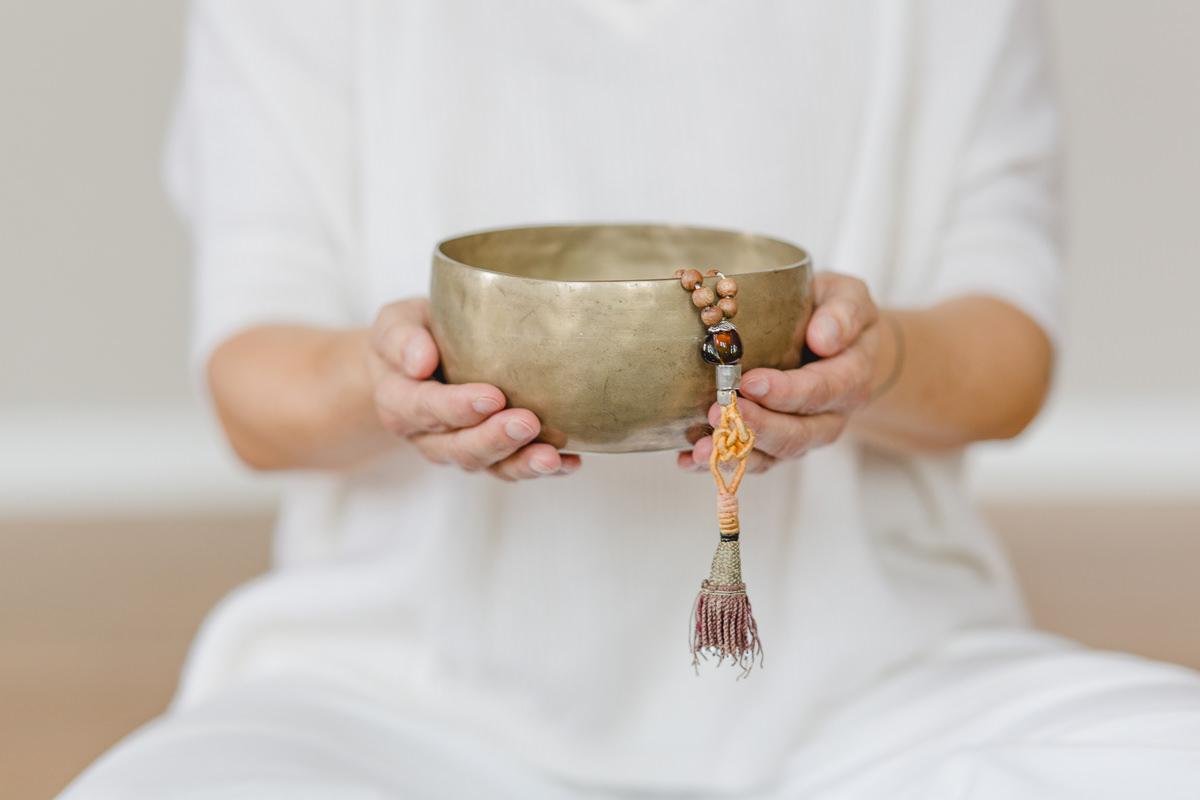 Portraitfoto einer Yogalehrerin, die eine Klangschale in der Hand hält