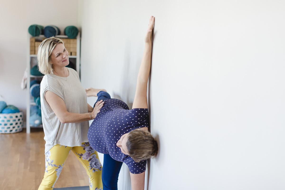 Yogafoto einer Yogalehrerin bei einer Yogaübung mit einer Schwangeren