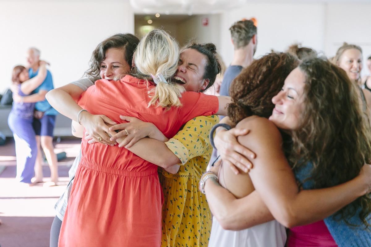 Teilnehmer der Closing Ceremony umarmen sich bei der Yoga Conference Germany 2019