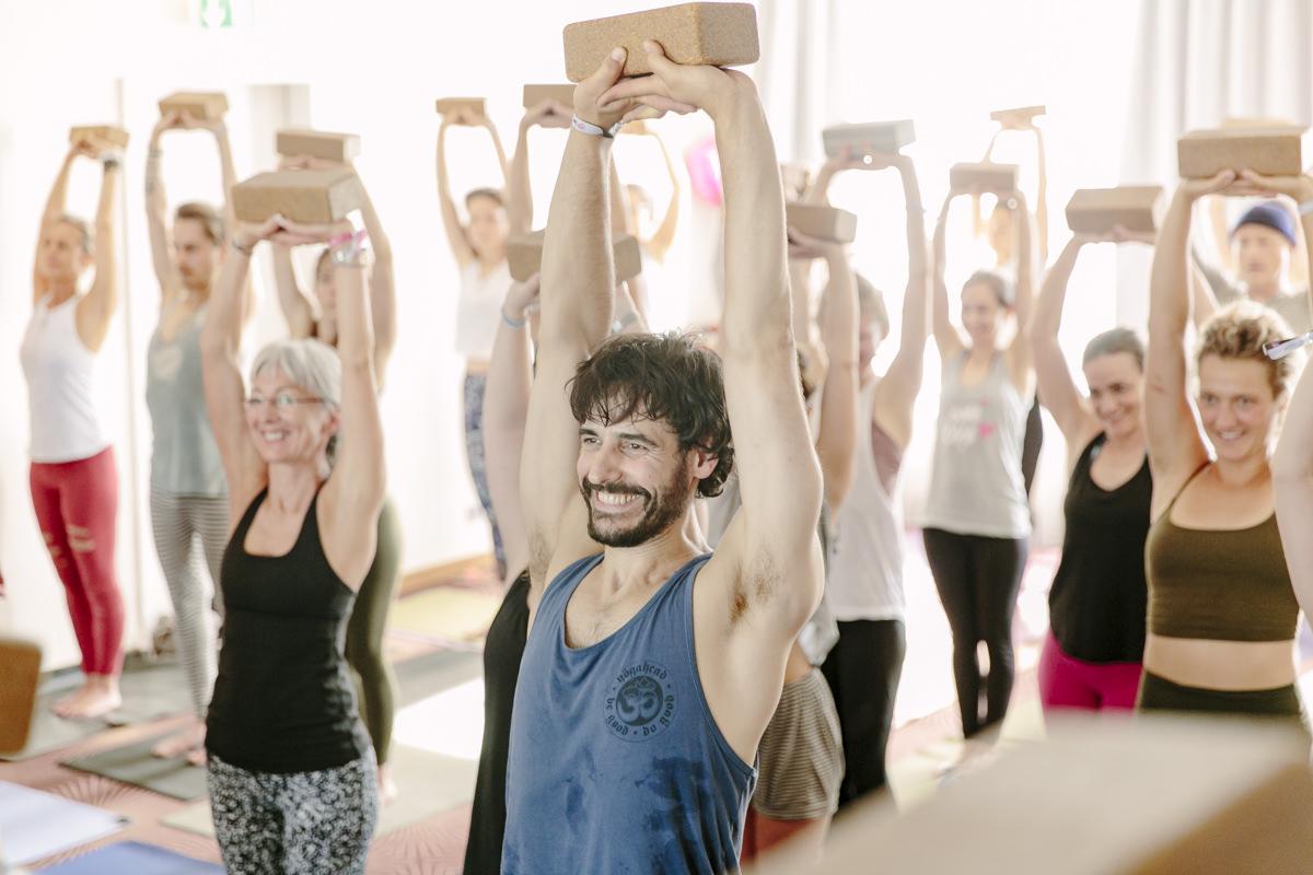 Teilnehmer eines Yoga Kurses strecken ihre Hände samt Yoga Block in die Luft bei der Yoga Conference Germany 2019