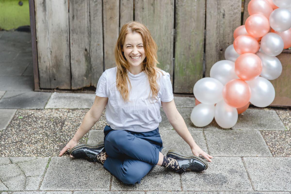 Outdoor Yoga Portraitfoto einer Yogalehrerin, die in der Stadt auf einem Gehweg sitzt