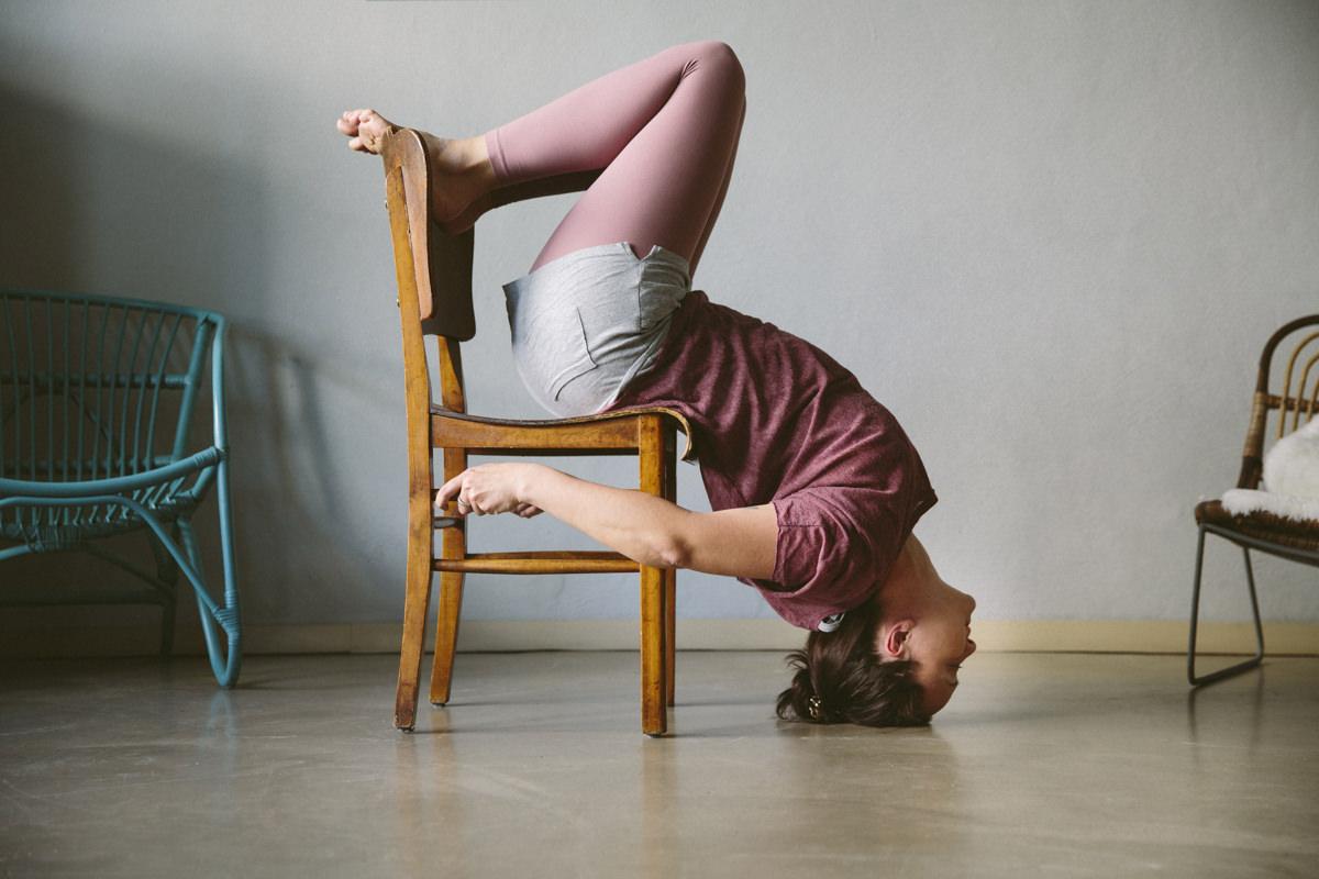 Yoga Portrait einer schwierigen Yogaübung mit einem Stuhl