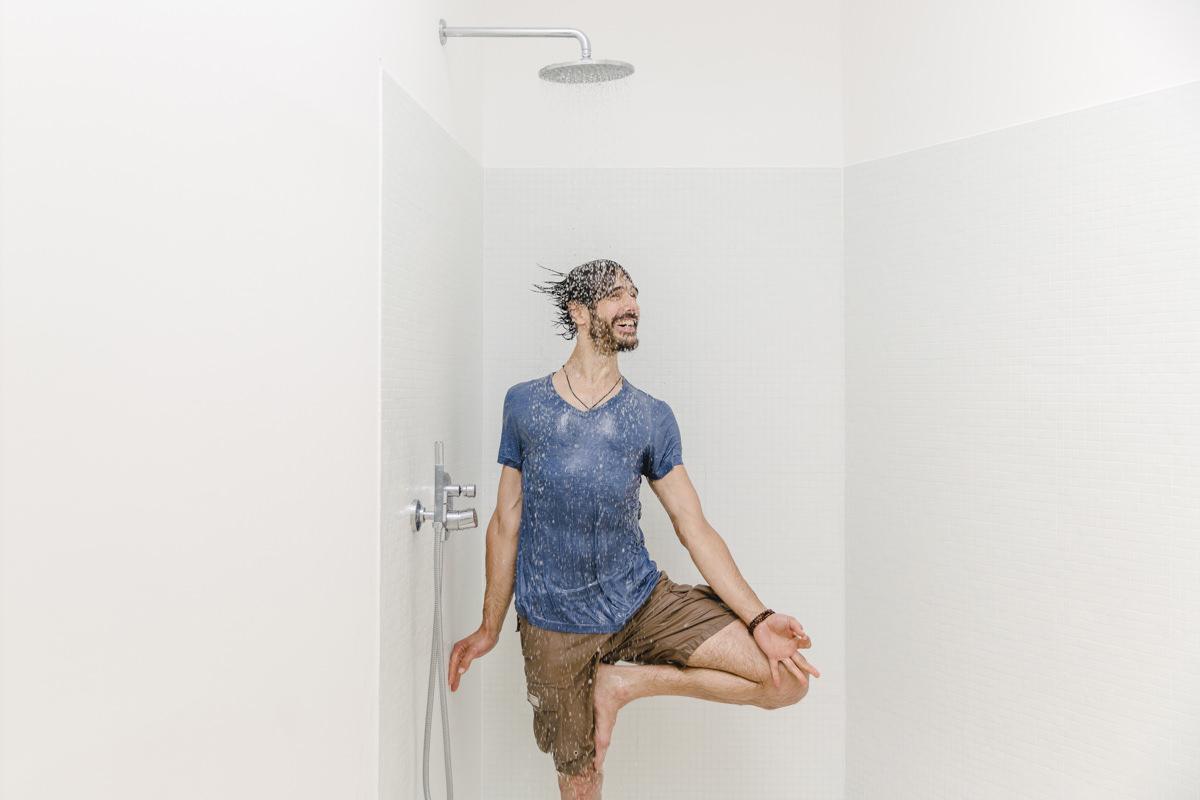 Yoga Portrait eines Yogalehrers, der bekleidet unter einer laufenden Dusche steht