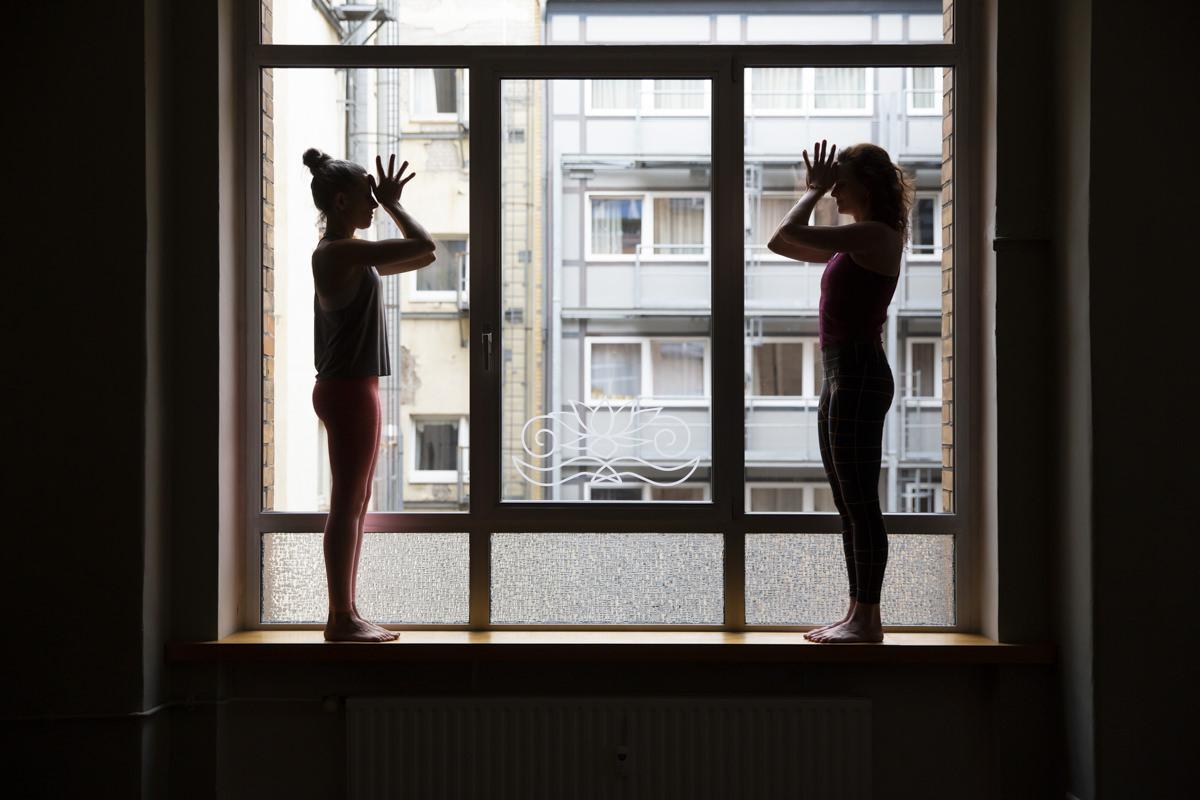 Yoga Portraitbild von 2 Yogalehrerinnen, die in Yogapose vor einem Fenster stehen