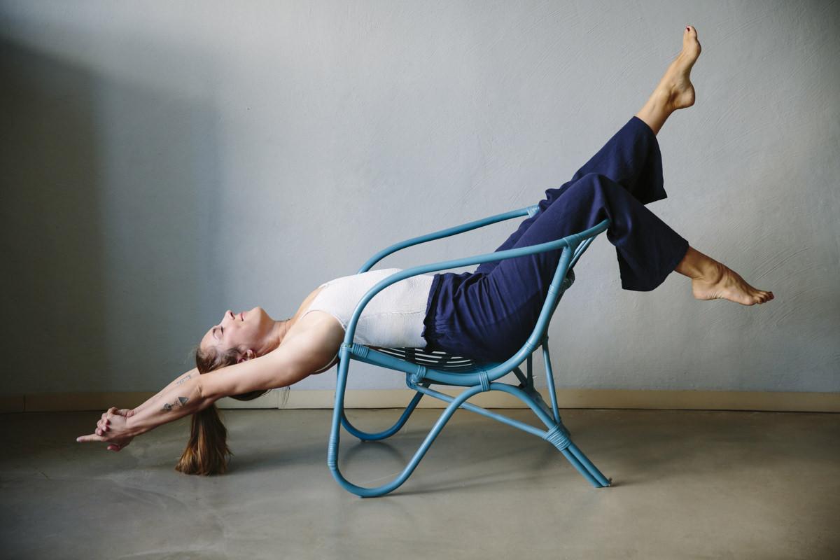 Yoga Portraitfoto von einer Yogalehrerin, die eine Yogaübung im Stuhl macht