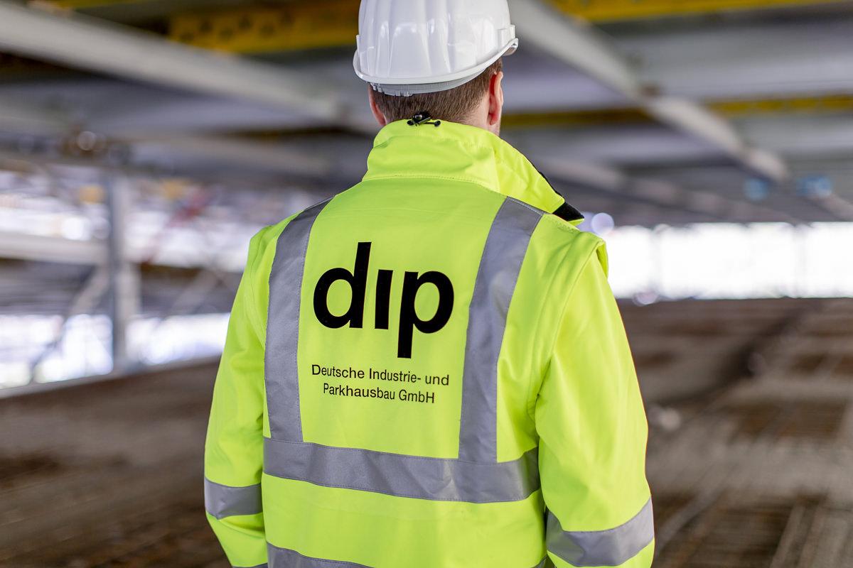 Rückenansicht eines Mitarbeiters mit gelber dip Arbeitsjacke